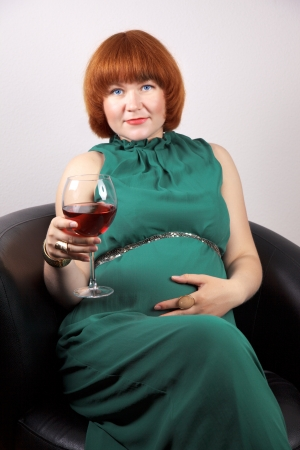 Pregnant elegant woman in evening dress with glass of red wine photo