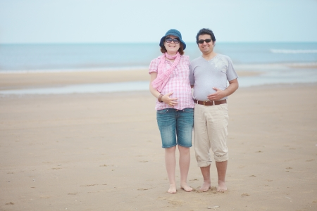 Happy couple expecting child, having vacation at seaside photo