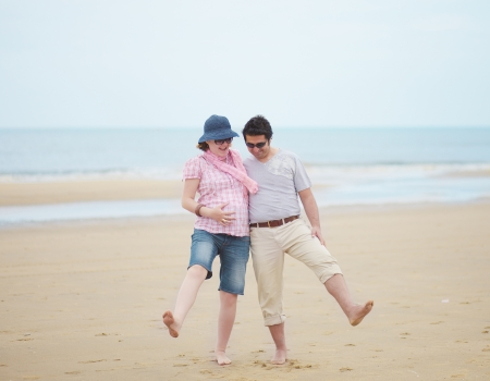 Happy playful couple expecting child, making fun on a beach