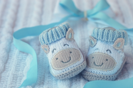 Knitted baby shoes for boy on a blue background  Greeting card  photo