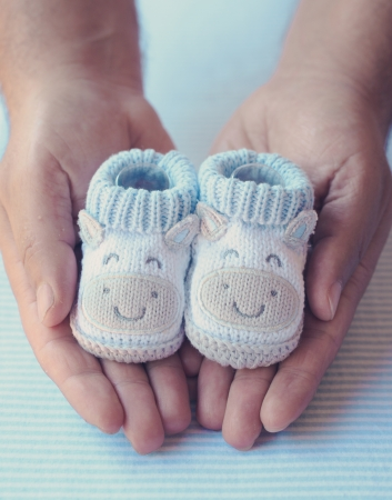 Father holds in his palms knitted baby shoes for boy photo
