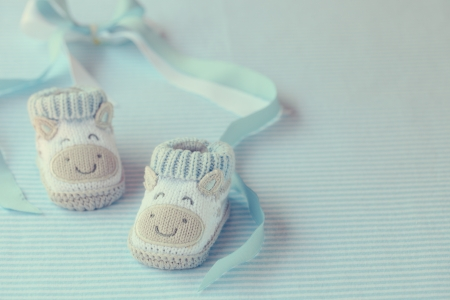 Knitted baby shoes for boy on a blue background. Greeting card. photo