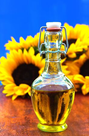 Bottle of sunflowers or olive oil on a colorful wooden background photo