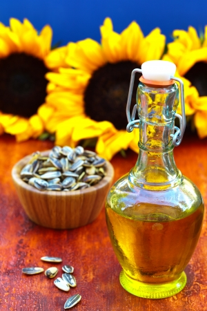 Bottle of sunflowers  oil on a colorful wooden background with sunflowers seeds photo