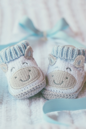 the lovely boy: Knitted baby shoes for boy on a blue background. Greeting card. Stock Photo