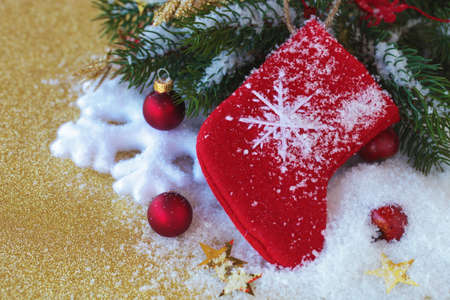 Christmas red sock with decoration on a gold background with snow and branch of pine Stock Photo - 15655644