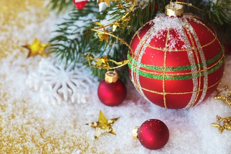Christmas red ball - decoration on a gold background with snow and branch of pine Stock Photo - 15655642