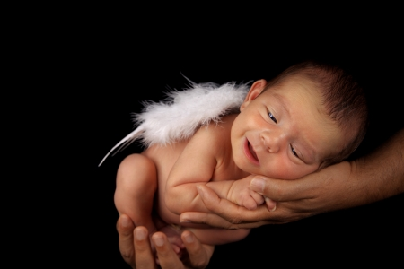 Smiling peacefull newborn baby boy with angel wings in father Stock Photo