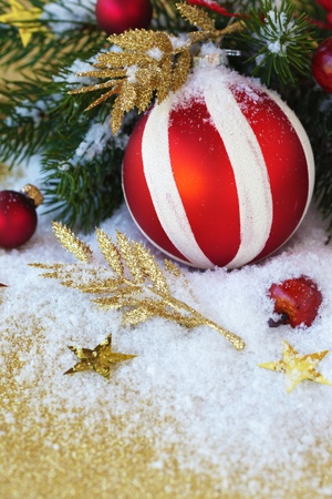 Christmas decoration on a gold background with snow and branch of pine Stock Photo - 15655645