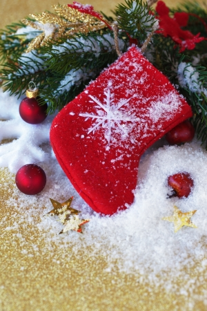 Christmas red sock with decoration on a gold background with snow and branch of pine Stock Photo - 15655646