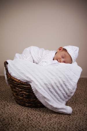 Adorable tiny newborn baby boy sleeping comfortable in a wicker photo