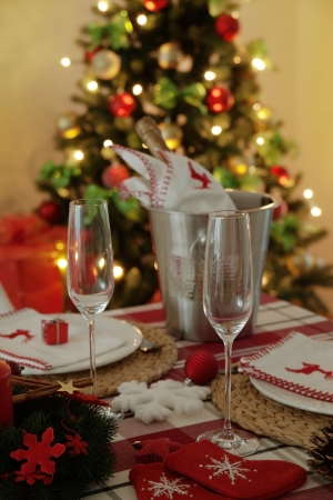 festive table setting. Cutlery and cooler with bottle of champagne, christmas tree with lights at the background