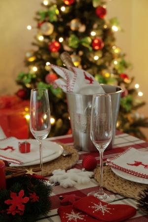 festlich gedeckten Tisch. Besteck und K�hler mit einer Flasche Champagner, Weihnachtsbaum mit Lichtern in den Hintergrund