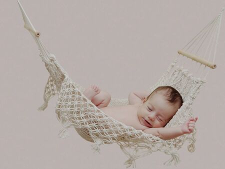 Adorable small baby stretching after sleeping in hammock Stock Photo