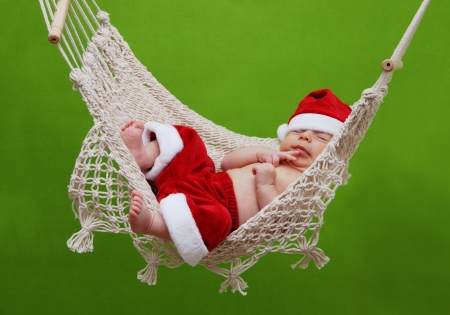 Baby boy sleeping in hammock with santa claus costume photo