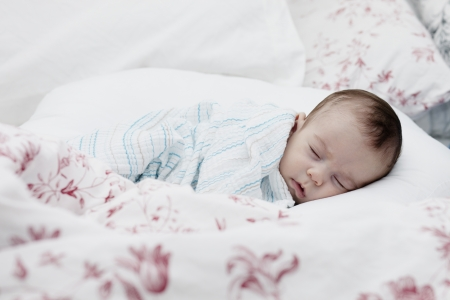 Tightly sleeping baby boy on his side with pillow and blanket. Stock Photo - 16522721