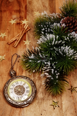christmas decoration in country style. Vintage clock with branch of pine on a wooden background photo