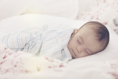 Tightly sleeping baby boy on his side with pillow and blanket  Stock Photo - 16765392