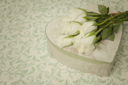 Heart shaped gift box with bouquet of white roses in vintage style photo