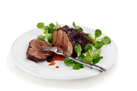 Grilled juicy fillet of beef with corn salad aside on a plate. Isolated, over white background.