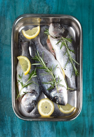 veggie tray: Fresh fish dorado in a cooking tray with herbs and lemons over wooden background