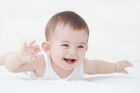 Schattige lachende baby jongen die zijn eerste tanden Stockfoto