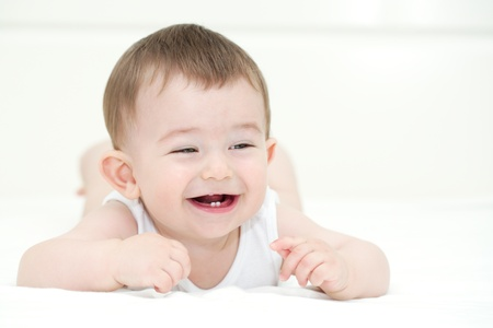 first teeth: Baby boy smiling and showing his first teeth. Indoors, close up with copy space Stock Photo