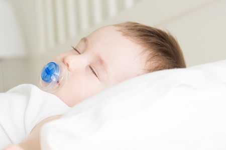 Adorable sleeping baby on the pillow with pacifier photo