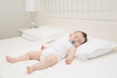 baby bed: Adorable baby sleeping relaxed and sprawl in parents bed Stock Photo