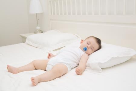 Adorable bebé relajado para dormir y la expansión en la cama de los padres Foto de archivo