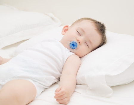 Adorable baby sleeping relaxed and sprawl in parents bed Stock Photo