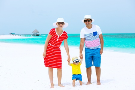 Happy family of three with sun glasses and hats standing on the beach  photo