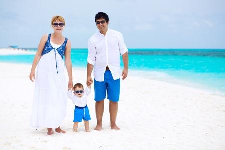 Happy family of three having tropical vacation photo
