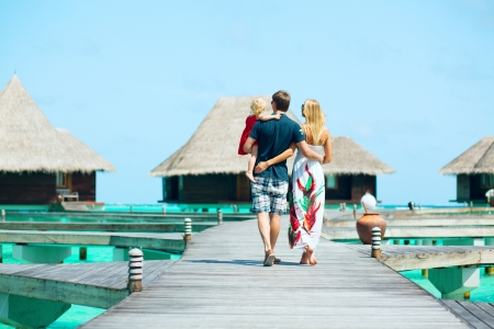 Family from back view having tropical vacation at Maldives, walking towards water bungalows photo