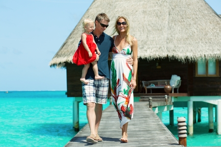 Happy family of three with water bungalow and turquoise water on background photo