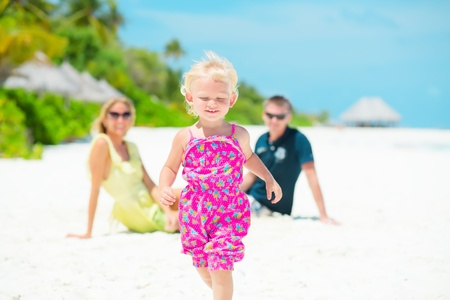 Running cheerful little girl having vacation with her parents  Stock Photo