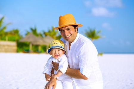 Happy father and son with panama hats and white clothes on the beach  photo