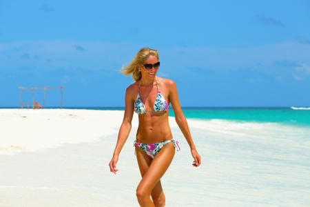 abdomen plano: Modelo de bikini hermosa que recorre en la playa en Maldivas Foto de archivo