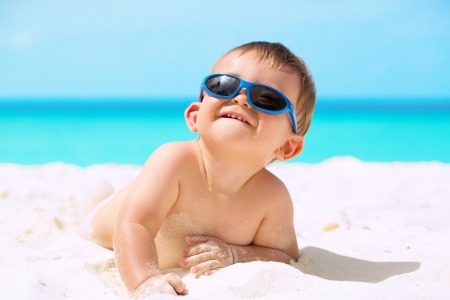 nude baby: Adorable funny baby with sunglasses lying on the white sandy beach and enjoying his first tropical vacation at Maldives Stock Photo
