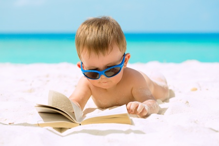 Cute baby boy with sunglasses lying on white sandy beach, reading the book and having his first tropical vacation