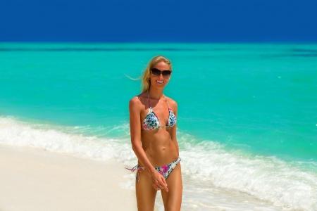 Beautiful bikini model walking on the beach at Maldives Stock Photo