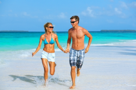 Cheerful sportive young couple running on the beach with tan and sunglasses   Stock Photo