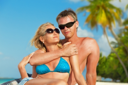 honeymooners: Young beautiful couple enjoying vacation at Maldives  Portrait with sunglasses and palm trees at background, close up
