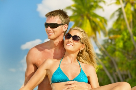 Young beautiful couple enjoying vacation at Maldives  Portrait with sunglasses and palm trees at background, close up   Stock Photo