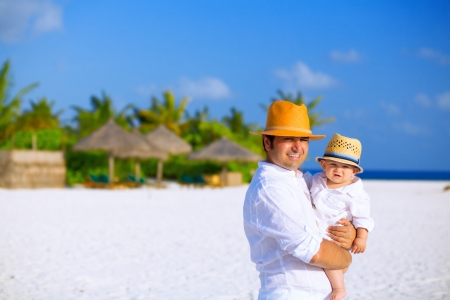 Father and son with panama hats stands on white sandy beach photo