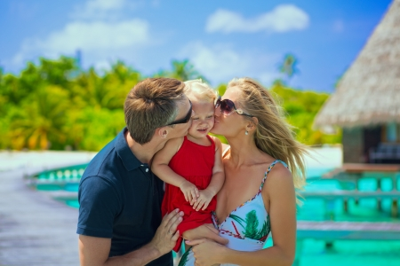 beach kiss: Happy parents kissing their daughter on the tropical beach  Stock Photo