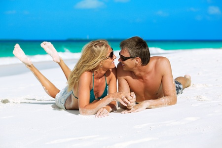 honeymooners: Young couple looking at each other with love, holding hands and enjoying their tropical vacation on Maldives Stock Photo