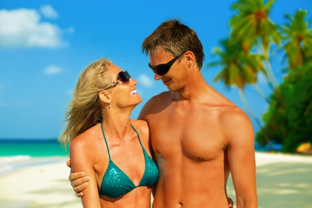 Young beautiful couple looking at each other and smiling on the white sandy beach at Maldives   photo