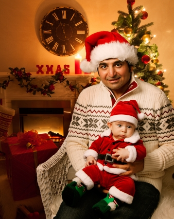 Christmas father and newborn cute baby with Santa Hats and decorated Christmas Tree with gifts and clock at background photo