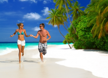 Happy young couple having fun, holding hands, looking at each other, running on the beach, having tropical vacation on Maldives Stock Photo